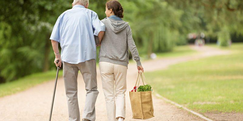 badante accompagna assistito a fare una passeggiata